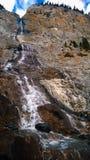 Berg die zonlicht en van de wolkencascade de daling van het bergwater verlengen Stock Afbeelding