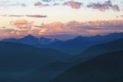 Berg efter solnedgång med härlig himmel och moln Arkivfoto