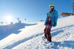 BERG ELBRUS, RUSSLAND - 30. NOVEMBER 2017: Ein Snowboardmädchen, das eine Sonnenmaske und einen Schal trägt, ist Stand auf Steigu Lizenzfreie Stockfotos