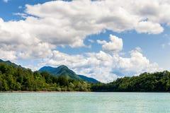 Berg en pluizige wolken over meer, Slovenië Stock Fotografie