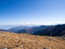 Berg Fujiyama durch Wolke mit blauem Himmel in Abstand und trockenem Wiesenhügel als Vordergrund Lizenzfreies Stockfoto