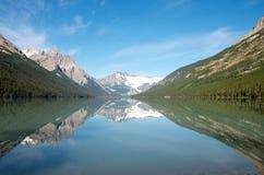Berg, glaciärer och träd reflekterade i en alpin sjö Royaltyfri Fotografi
