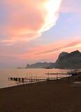 Berg havet, sandig strand på solnedgången Royaltyfria Foton