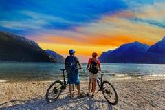 Berg het biking, paar met fietsen bij zonsondergang op Meer Garda, Riva stock foto's