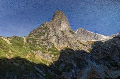 Berg in het meer wordt weerspiegeld dat Stock Foto