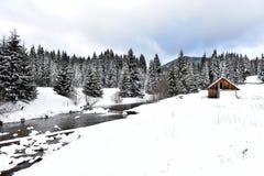Berg houten die chalet met verse sneeuw wordt behandeld stock foto