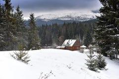 Berg houten die chalet met verse sneeuw wordt behandeld royalty-vrije stock afbeeldingen