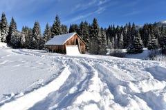 Berg houten die chalet met verse sneeuw wordt behandeld stock foto's