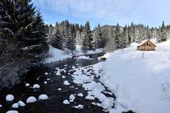 Berg houten die chalet met verse sneeuw wordt behandeld stock fotografie