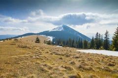 Berg i blåsig solig dag med det över huvudet molnet Fotografering för Bildbyråer