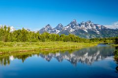 Berg i den storslagna Teton nationalparken med reflexion i Snake River Arkivfoto