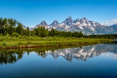 Berg i den storslagna Teton nationalparken med reflexion i Snake River Arkivbilder