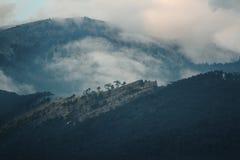 Berg i moln på solnedgången Arkivbilder