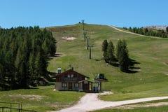 Berg i sommar Tid: Ski Lift, typisk hus och gräsplanäng Arkivfoto