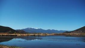 Berg i spegel av Lugu sjön arkivfoton