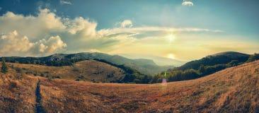 Berg i strålarna av resningsolen Arkivfoto