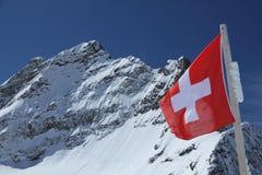 Berg Jungfrau hinter der Flagge von der Schweiz Stockfotografie