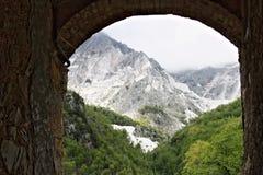 Berg med Carrara de vita marmorvillebråden som ses från Colonnata Den forntida staden av marmorerar quarrymen är berömd för royaltyfri foto