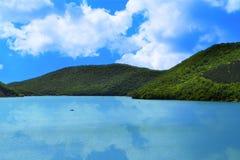 Berg med den gröna skogen på en sjökust på den ljusa blåa himlen med molnbakgrund Royaltyfri Fotografi