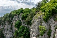 Berg med en brant stenig lutning En man sitter extremt på kanten av en klippa fotografering för bildbyråer