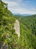 Berg med en brant stenig lutning och dal med den tjocka gröna skogen under fotografering för bildbyråer