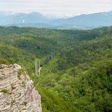 Berg med en brant stenig lutning och dal med den tjocka gröna skogen under royaltyfria bilder