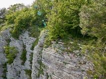 Berg med en brant stenig lutning och dal med den tjocka gröna skogen under arkivfoton