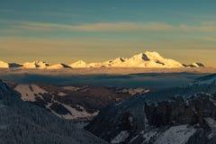 Berg med en soluppgång som omges av moln royaltyfri foto