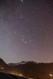 Berg med liten snö på överkanten i natten för purpurfärgad och mörk färg med stjärnor i vinter på Lachung i norr Sikkim, Indien Fotografering för Bildbyråer