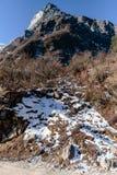 Berg med snö och sidor mindre träd Nedanför med grusvägen på vägen till nollpunkt på Lachung i vinter Norr Sikkim, Indien Arkivbilder