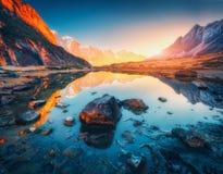 Berg med upplysta maxima, stenar i bergsjön på solnedgången royaltyfri foto