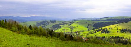 Berg met groene heuvels en pijnboombomen op de hellingen van een bewolkte bewolking royalty-vrije stock foto