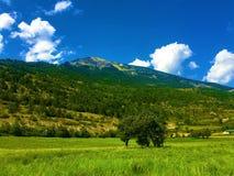 Berg, moln, himmel och fältet royaltyfria bilder