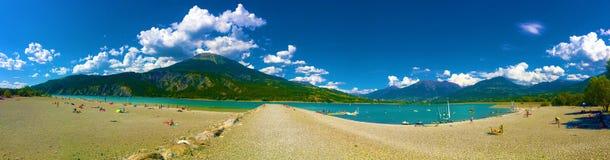Berg, moln, sjö och stranden royaltyfri fotografi
