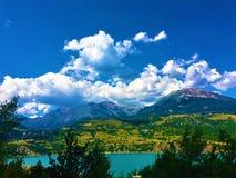 Berg, moln, träd och sjö royaltyfria foton