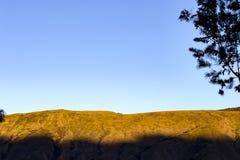 Berg mot en klar blå himmel på solnedgången royaltyfri foto