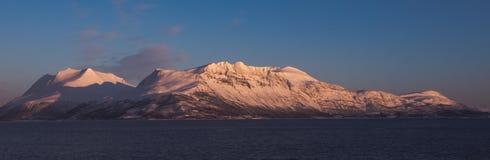 Berg nära Tromso Taget från kuster på Bakkejord, nära Tromso Norge, mars 2019, solnedgång arkivfoton