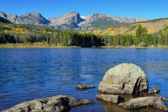 Berg och alpin sjö med reflexion i nedgången Arkivbild