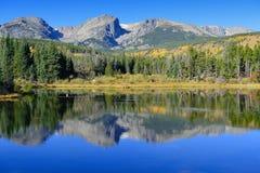 Berg och alpin sjö med reflexion i nedgången Arkivbilder
