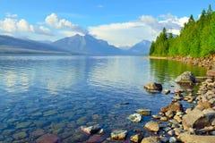 Berg och banken av McDonald sjön i glaciärnationalpark Arkivfoton