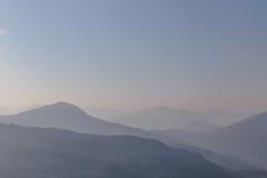 Berg och dimma med apelsinen som gör suddig himmel i morgonen i vinter i Gangtok Norr Sikkim, Indien Arkivfoto