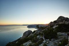 Berg och hav på solnedgången arkivfoton