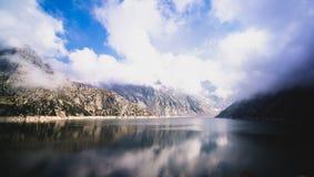 Berg och himmelreflexion i sjön arkivfoto