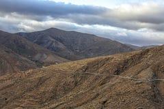 Berg och mörka moln av Fuerteventuras landskap arkivbild