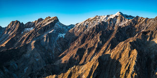 Berg och marmor för den Apuane alpien bryter sten snöig på solnedgången i winte royaltyfri bild