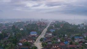 Berg och by med mist Arkivfoto