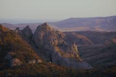 Berg och mest forrest kullar på den rosa solnedgången Arkivbild