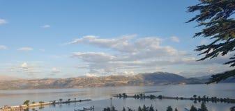 Berg och moln vid sjön arkivbild