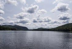 Berg och sjö med fluffiga moln Arkivbild