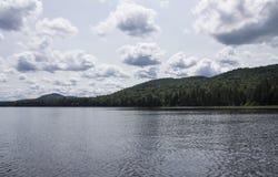 Berg och sjö med fluffiga moln Royaltyfria Bilder